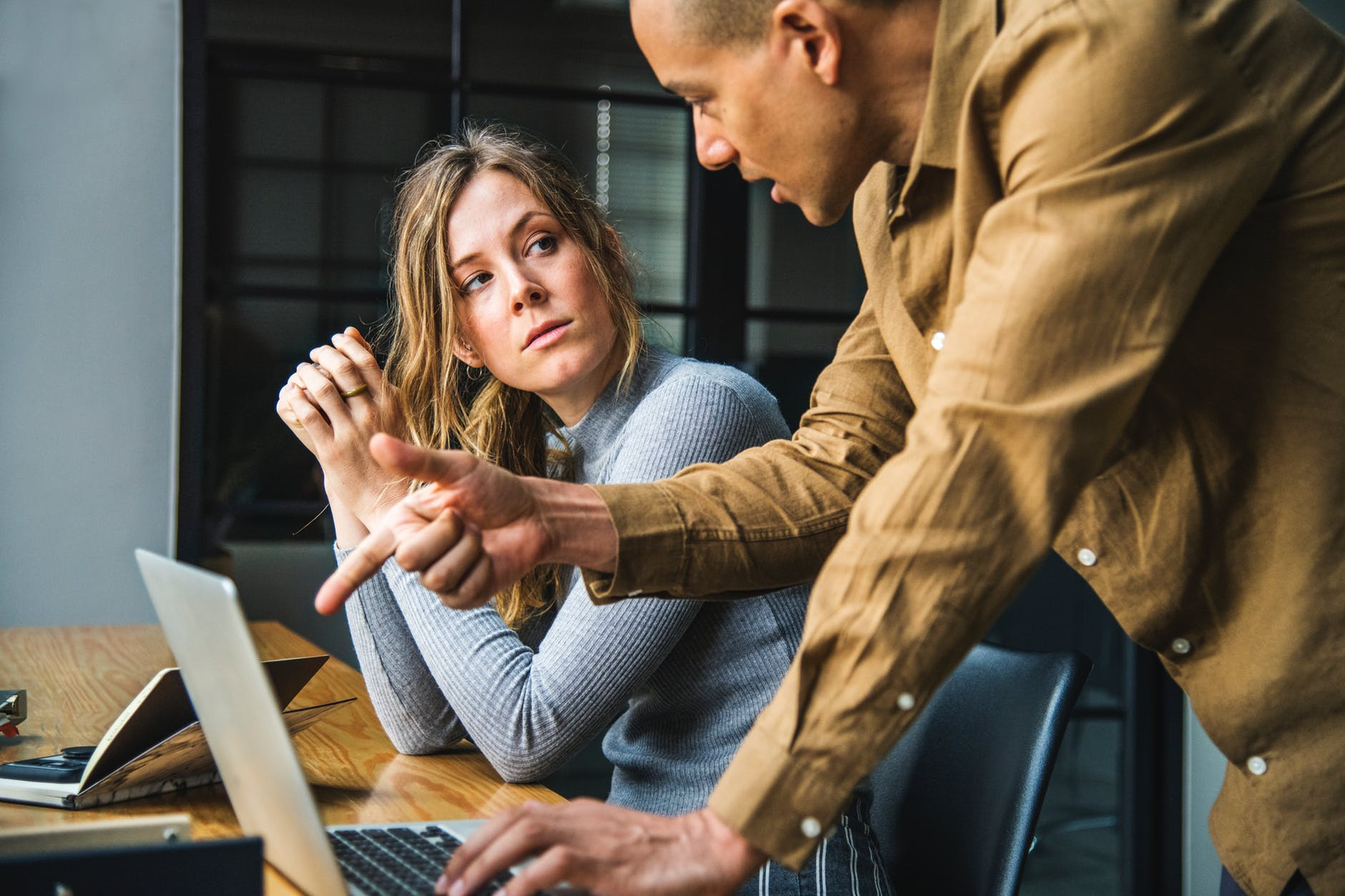man in brown long sleeved button up shirt standing while using gray laptop computer on brown wooden table beside woman in gray long sleeved shirt sitting
